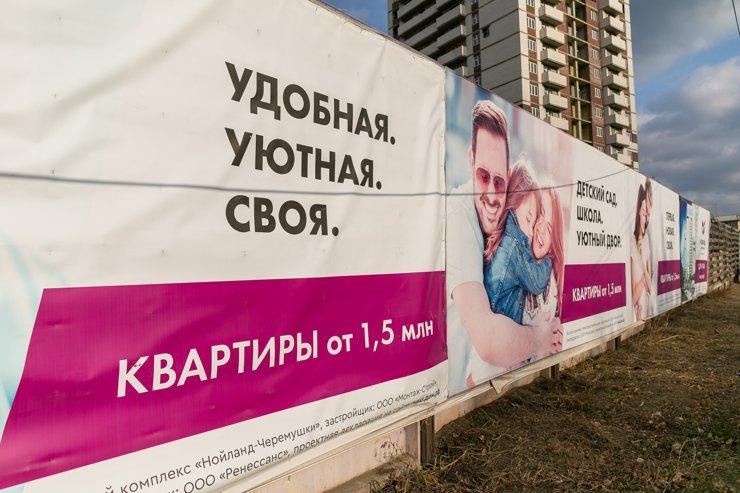 Баннеры на заборе стройки соблазняют лозунгами для молодых семей